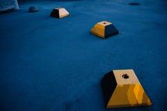 Het concrete blok van de beknotte gele piramide tegen de achtergrond van blauw asfalt stock afbeelding