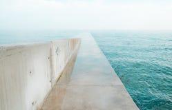 Het concrete dok uitrekken zich uit aan overzees stock foto's