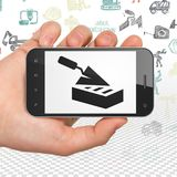 Het construeren van concept: Handholding Smartphone met Bakstenen muur op vertoning Royalty-vrije Stock Fotografie