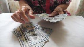 Het contante geld van de grootmoederholding in handen en tellende vreemde valuta over lijst De wapens van oude vrouw overweegt ho stock video
