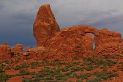 Het contrast van Grey Threatening sky's met de Rode Rotsbogen stock afbeeldingen