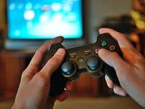 Het controlemechanisme van de videospelletjeconsole voor gokken in gamershanden die wordt gehouden stock foto