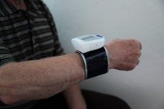 Het controleren van bloeddruk Sluit omhoog mening van een bloeddrukmonito op hand Digitale tonometr op menselijke hand Metend haa stock foto's