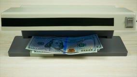 Het controleren van de dollars in de muntdetector Eindemotie stock footage