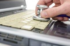 Militair die oude laptop met stethoscoop controleren Royalty-vrije Stock Foto's