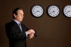 Het controleren van de tijd. Zekere rijpe zakenman die zijn w bekijken royalty-vrije stock afbeelding