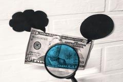Het controleren van dollars vervalsing Vergrootglas tegen de achtergrond van een bankbiljet royalty-vrije stock fotografie