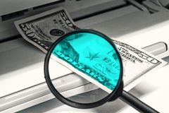 Het controleren van dollars vervalsing Vergrootglas tegen de achtergrond van een bankbiljet en een printer royalty-vrije stock afbeeldingen