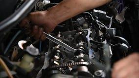 Het controleren van een motor van een auto reparatie bij autogarage stock videobeelden