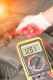 Het controleren van het voltage van de autobatterij Stock Afbeeldingen