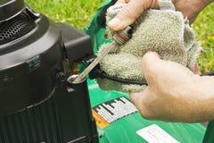 Het controleren van olie op een grasmaaimachine Royalty-vrije Stock Afbeelding