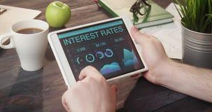 Het controleren van rentevoetengegevens die tabletcomputer met behulp van bij bureau stock footage