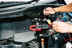 Het controleren van vermogen van batterij door klemmeter, stock foto's