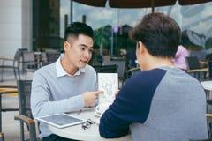 Het controleren van Voorraden Twee partners die aan laptop werken die cheerfully op een vergadering bij de lokale koffie glimlach stock foto's