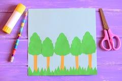 Het creëren van de kaart van de Aardedag stap gids De kaart van de aardedag met bomen en gras, schaar, lijmstok, potlood, malplaa Stock Afbeelding