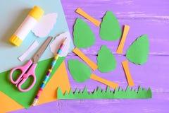 Het creëren van de kaart van de Aardedag stap leerprogramma Bomen en grasbesnoeiing van gekleurd document, schaar, lijmstok, potl Stock Foto