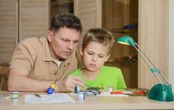 Het creëren van het modelvliegtuig De gelukkige zoon en zijn vader maken vliegtuigenmodel Hobby en familieconcept Stock Afbeelding