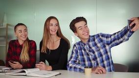 Het creatieve commerciële team in modern bureau stelt voor selfie met een telefoon Portret van het glimlachen het toevallige comm stock videobeelden