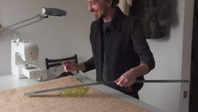 Het creatieve patroon van de de tekeningskleding van de mensenkleermaker op vindend document in het naaien van workshop stock video