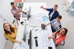 Het creatieve team met computers het tonen beduimelt omhoog Royalty-vrije Stock Foto's