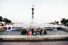 Het creatieve Team van Aantrekkelijke Tienermeisjes stelt in openlucht in het Park dichtbij de Fonteinen Stock Foto