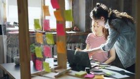 Het creatieve team van vrouwelijke ontwerpers werkt aan nieuw project, delend ideeën, schrijvend informatie over gekleurde sticke stock footage