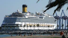 Het cruiseschip ongeveer om weg te gaan dokte in de haven met mensen op strand en industriële kranen stock videobeelden