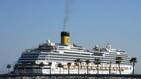 Het cruiseschip ongeveer om weg te gaan dokte in de haven met mensen op strand en industriële kranen stock footage