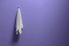het 3D teruggeven: illustratie van een stuk van het schone en witte handdoek hangen op een purpere pastelkleurmuur, een licht en  Stock Fotografie