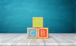 het 3d teruggeven van drie stuk speelgoed blokken van verschillende kleuren met brieven A, B en C op hen die zich op een houten b Stock Fotografie