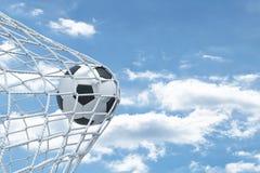 het 3d teruggeven van een voetbalbal onbekwaam om het net van de poorten met bewolkte hemel op de achtergrond te scheuren royalty-vrije illustratie