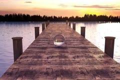 het 3d teruggeven van kristallen bol op houten brug in de ochtend lig Stock Afbeelding
