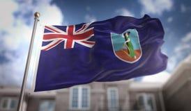 Het 3D Teruggeven van Montserrat Flag op Blauwe Hemel de Bouwachtergrond Stock Foto's