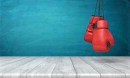 het 3d teruggeven van twee rode bokshandschoenen die boven een houten bureau voor een blauwe bordachtergrond hangen Royalty-vrije Stock Afbeelding