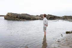 Het dagdromen van de jongen op strand stock fotografie