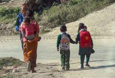 Het dagelijkse leven in Nepal, kinderen in eenvormige gang hand in hand aan school, moeder vervoert een klein kind terug op haar royalty-vrije stock foto's