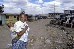 Het dagelijkse levensvrouwen met gehandicapt kind, krottenwijk Nairobi stock afbeelding