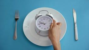 Het dagelijkse regime, wekker op plaat, hangt dieettijd aan, juiste voeding stock afbeelding