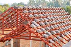 Het dak in aanbouw met stapels daktegels voor huis bouwt Stock Foto's