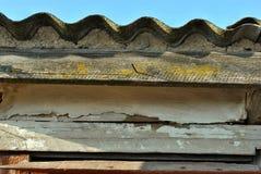 Het dak van de leischuur met golvende lijn en sjofele houten plank met geel mos op blauwe hemelachtergrond stock fotografie
