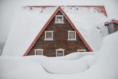 Het dak van een blokhuis Grote sneeuwafwijkingen Driehoekig dak met vensters stock afbeeldingen