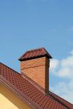 Het dak van een modern huis met baksteenschoorsteen Stock Foto's