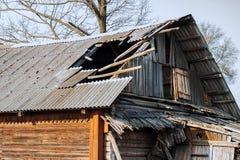 Het dak van een oud houten geruïneerd huis onder de struiken stock afbeelding