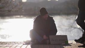 Het dakloze mannetje die van de oorlogsveteraan op de straat bedelen stock videobeelden