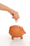 Het dalen van de hand muntstuk in spaarvarken Stock Fotografie