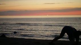Het dansen bij zonsondergang op het strand stock videobeelden