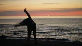 Het dansen bij zonsondergang op het strand stock footage