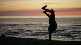 Het dansen bij zonsondergang op het strand stock video