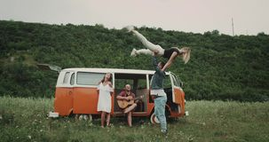 Het dansen tijd voor groep vrienden bij de aard, die op de gitaar spelen, die in de retro bestelwagen zitten 4K stock video
