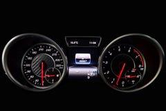 Het dashboard van de auto is het gloeien blauw met rode pijlen bij nacht met een snelheidsmeter, tachometer en andere hulpmiddele stock afbeeldingen